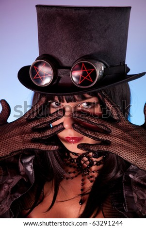 Portrait of gothic girl wearing tophat with pentacles, Halloween theme - stock photo