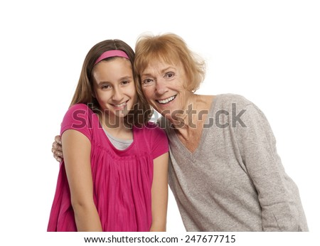 Portrait of granddaughter and grandmother embracing against white background - stock photo