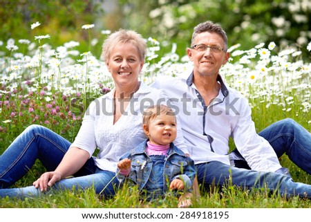 Portrait of Granddaughter and Grandparents sitting Outside At The Park.