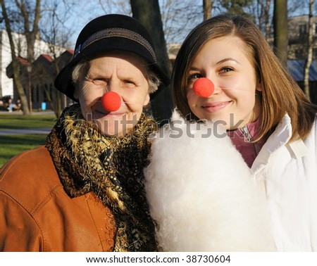 Portrait of Granddaughter and granny with clown noses rest in autumn park - stock photo