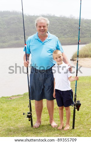 portrait of grandfather and grandson standing by lake with fishing rods - stock photo