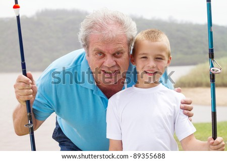 portrait of grandfather and grandson with fishing rods - stock photo