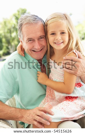 Portrait Of Grandfather With Granddaughter Relaxing Together On Sofa - stock photo