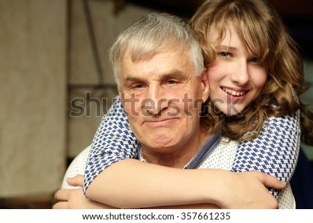 Portrait of grandfather with his granddaughter indoor - stock photo