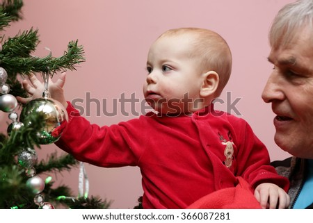 Portrait of grandfather with his grandson near christmas tree - stock photo