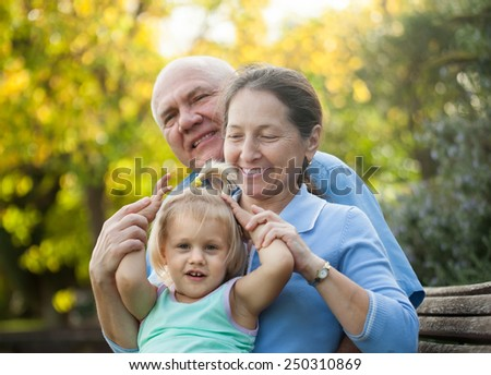 Portrait of grandma and  grandpa with little grandaughter  outdoor - stock photo