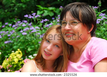 Portrait of grandmother and granddaughter in a garden - stock photo