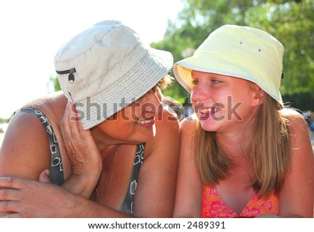 Portrait of grandmother and granddaughter lying on a sandy beach - stock photo
