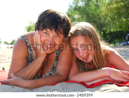 Portrait of grandmother and granddaughter lying on a sandy beach