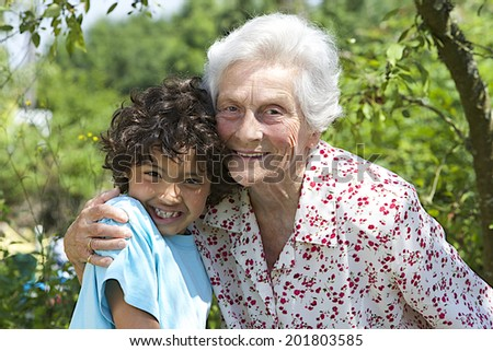 Portrait of Grandmother and  happy grandson in sunny garden  - stock photo