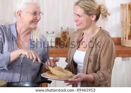 portrait of grandmother offering crepes - stock photo