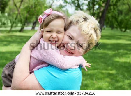 Portrait of grandmother with her little granddaughter outdoor - stock photo