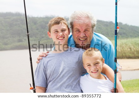 portrait of grandpa and grandsons fishing - stock photo