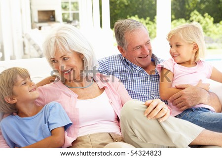 Portrait Of Grandparents With Grandchildren Relaxing Together On Sofa - stock photo
