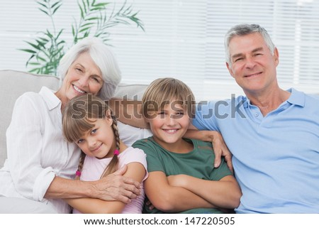Portrait of grandparents with their grandchildren sitting on couch - stock photo