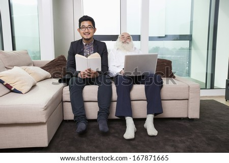 Portrait of grandson reading book while grandfather using laptop on sofa at home
