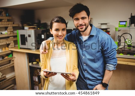 Portrait of graphic designers holding digital tablet in office