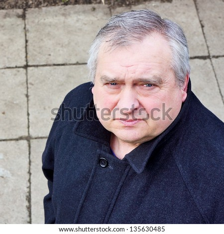 Portrait of grey-haired mature man in a black coat - stock photo