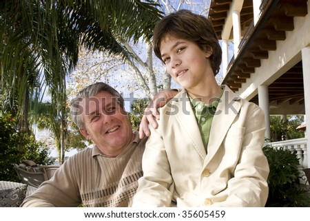 Portrait of grinning father and son outdoors