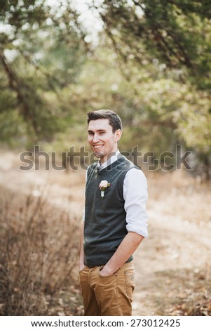 portrait of groom. groomsman. handsome man in spring park. male portrait with hands in pockets. young man in spring park