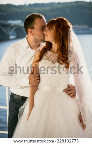 Portrait of groom kissing redhead bride at sunny day on riverbank - stock photo