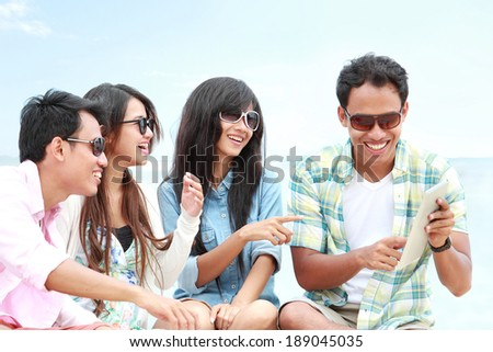 portrait of Group Friends Enjoying Beach Holiday together with tablet pc. technology and internet concept - stock photo