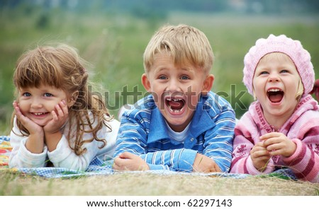 portrait of group laughing children lying on the grass - stock photo