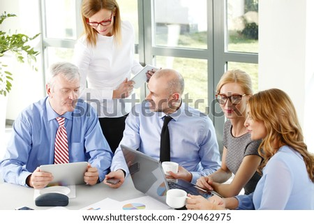 Portrait of group of businesswomen and businessmen sitting around conference table.  Business people working with laptop and digital tablet while consulting and analyzing diagrams. - stock photo