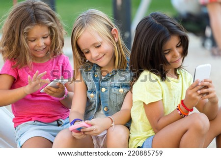 Portrait of group of childrens chatting with smart phones in the park.