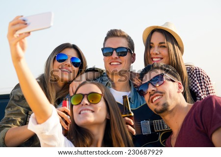 Portrait of group of friends taking a selfie with smartphone.  - stock photo