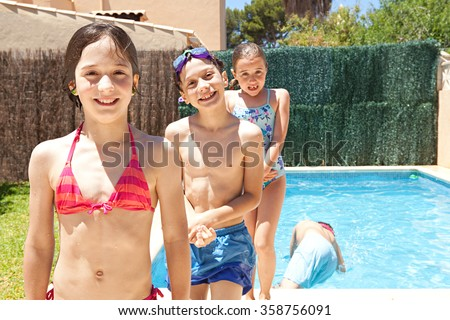 Portrait of group of joyful children having fun by swimming pool in a home garden on a sunny summer holiday, smiling together outdoors. Active kids lifestyle, playing in house exterior on vacation.