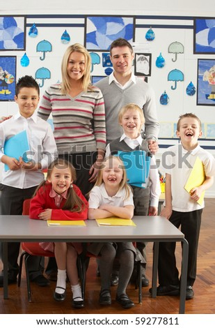 Portrait Of Group Of Primary Schoolchildren And Teachers Sitting At Desk In Classroom