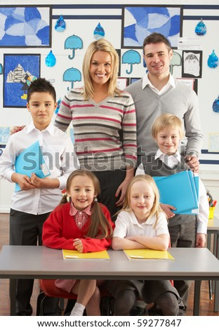 Portrait Of Group Of Primary Schoolchildren And Teachers Sitting At Desk In Classroom - stock photo