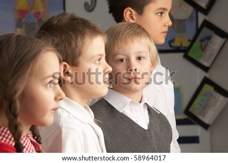 Portrait Of Group Of Primary Schoolchildren Standing In Classroom