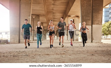 Portrait of group of runners from running club under a bridge. Young men and women jogging together. - stock photo