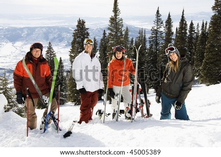 Portrait of group of skiers standing on ski slope in Colorado smiling with a valley in background - stock photo