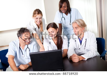 Portrait of group of smiling hospital colleagues looking at the laptop and discussing - stock photo