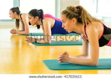 Portrait of group of sporty people doing aerobic class on a fitness center.