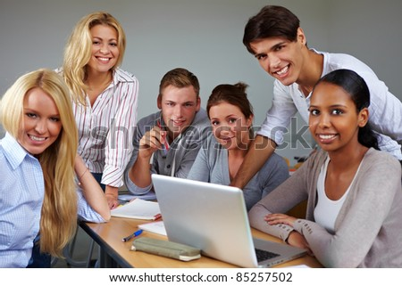 Portrait of group of students around laptop