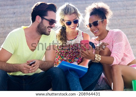 Portrait of group of university students using mobile phone in the street. - stock photo