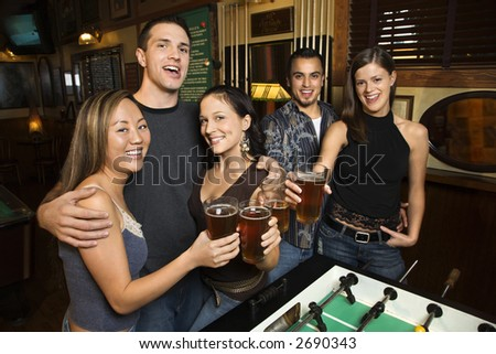 Portrait of group of young friends hanging out in pub and drinking beer. - stock photo