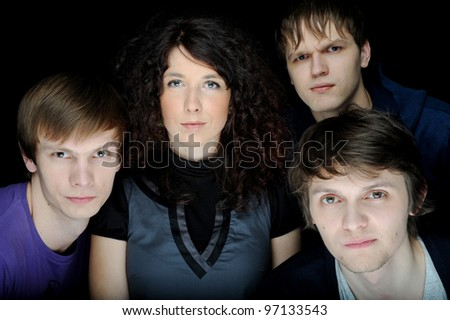 Portrait of group of young friends together isolated on black - stock photo