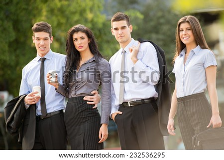 Portrait of group of young successful business people dressed in suits,on coffee break standing outside, smiling looking at camera.