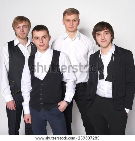 Portrait of group young men standing over white background looking at camera - stock photo