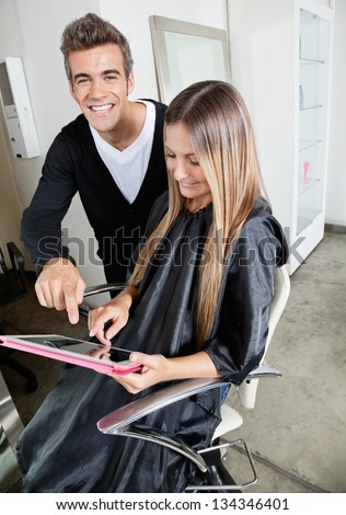 Portrait of hairdresser and female customer with digital tablet in beauty parlor - stock photo