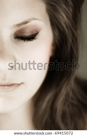 Portrait of half a young womans face with eyes closed in muted tones.