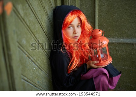 Portrait of Halloween girl with red hair holding lantern with candle - stock photo