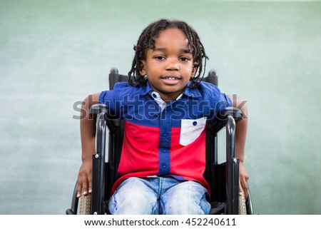Portrait of handicapped boy against board in classroom - stock photo
