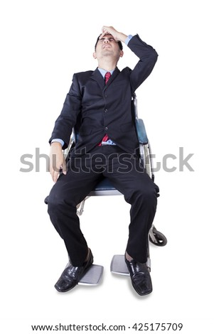 Portrait of handicapped businessman sitting on the wheelchair and looks dizzy, isolated on white background - stock photo