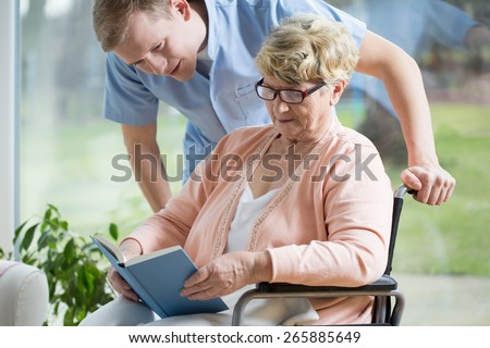 Portrait of handicapped senior woman reading book - stock photo